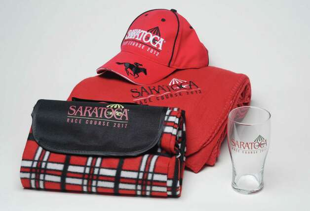 Saratoga Race Course giveaways for the 2012 meet; picnic mat, Aug. 12, left, fleece blanket, Sep. 2, baseball hat, July 29, and pilsner glass, Aug. 19, right. Each giveaway is free with paid admission to the track. Photo taken Monday June 25, 2012 in Colonie, N.Y. (Will Waldron / Times Union)