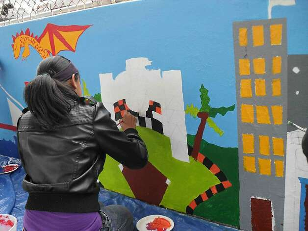 Students at Buena Vista Horace Mann K-8 school in San Francisco paint the first part of a mural along the Bartlett Street wall in 2011. Photo: Courtesy Photo, Megan McMahon