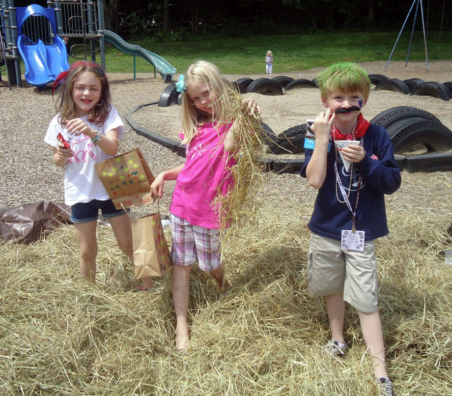 Royle wranglers Josie Herbert, Emma Quayle and Jeb Bennett sift through bales of hay looking for candy. Darien, Conn. Photo: Contributed Photo