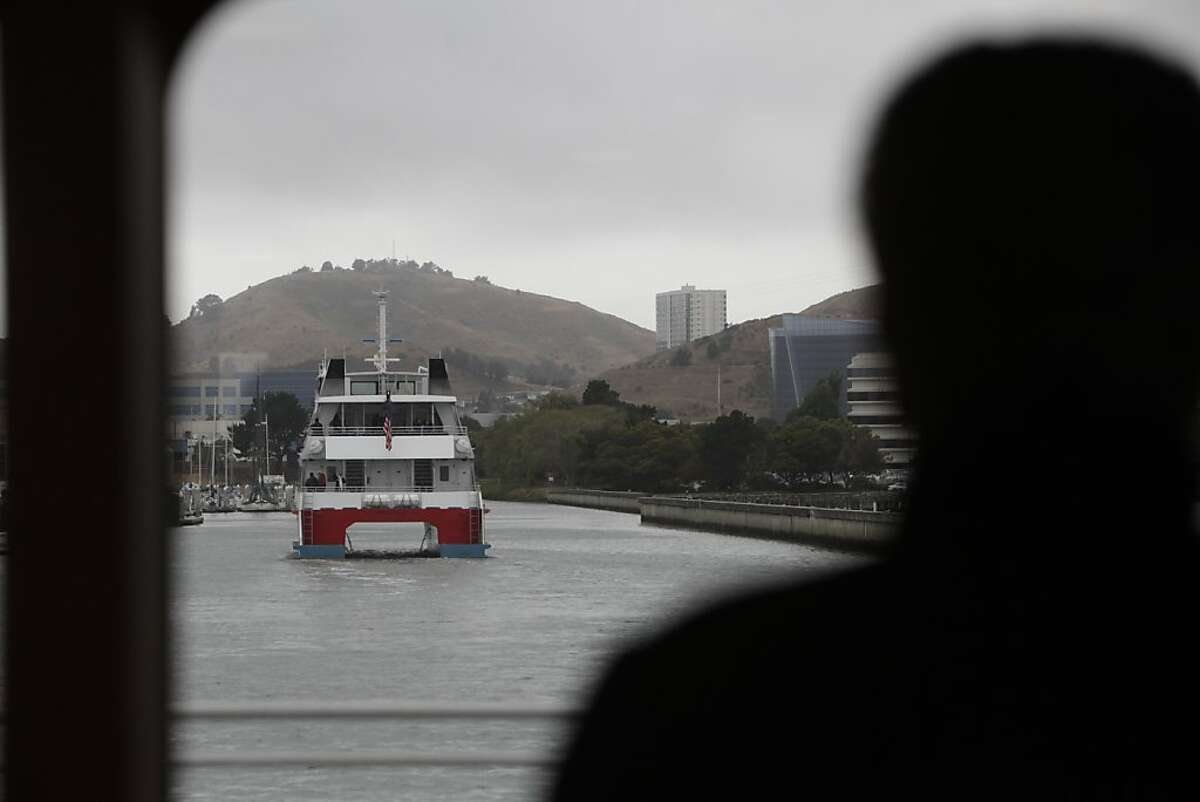 A passenger aboard the ferry Gemini watches the ferry Pisces (left) head back to the Oyster Point Marine Ferry Terminal after a bay cruise during the San Francisco Bay Ferry South San Francisco Inaugural Celebration.