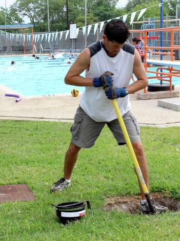 Chris Rios, volunteer board member for Colonies House, digs a hole to fix an underground pipe June 7 while Colonies House swim team members practice. Rios is just one of 10 board members who finds himself at the neighborhood complex frequently to keep up with the continuous maintenance. Photo: Melody C. Mendoza / North Central News
