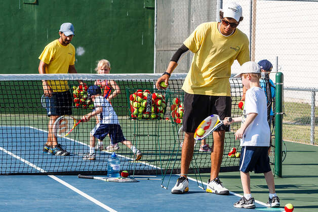 Tennis coaches Joey Gdovin (right) and Daniel Rubio work with young tennis players during the elementary QuickStart morning camp for children ages 10 and under Monday at the North East ISD Tennis Center. The camp runs through Aug. 9. Photo: Marvin Pfeiffer / North Central News / Prime Time Newspapers 2012