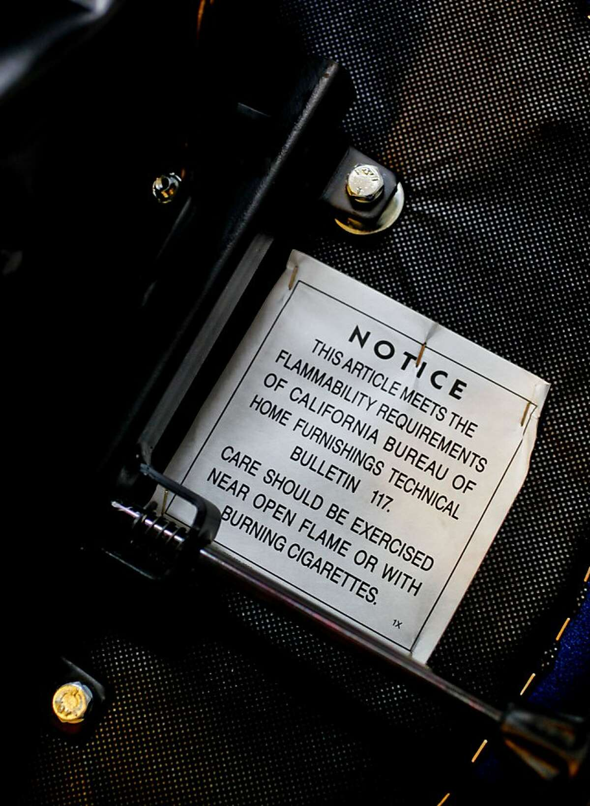 The same warning label used since 1975 is visible on the bottom of a desk chair at the home Judy Levin, in Oakland, Ca., on Friday June 22, 2012. California has the opportunity to set the tone for a new national furniture fire-safety standard to replace the state's decades-old requirement that had led to the use of toxic flame retardants in couches, chairs and baby product sold throughout North America.