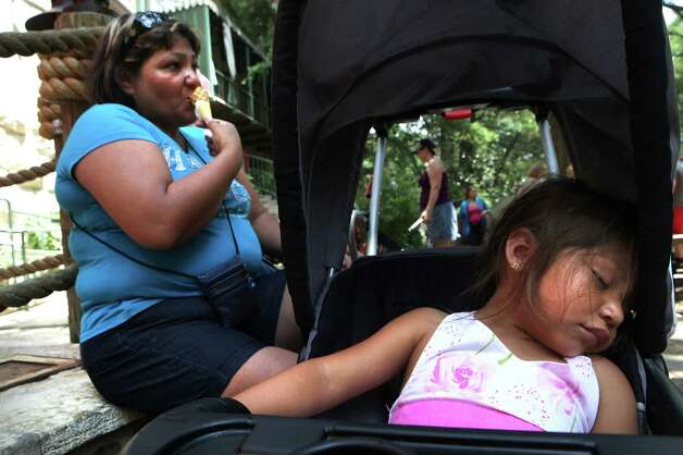 Claudio De La Rosa, left, eats an ice cream cone on the River Walk as her grand daughter Leah Ayala, 2, naps exhausted from the heat.  Monday, June 25, 2012. Photo: BOB OWEN, San Antonio Express-News / © 2012 San Antonio Express-News