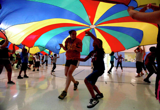 Kids in the City of San Antonio's Parks and Recreation program called the Summer Youth Program play with a parachute at the Garza Community Center Monday June 25, 2012. The program gets the kids out of the heat and lasts from June 18 to August 10. Photo: John Davenport, San Antonio Express-News / John Davenport/San Antonio Expre