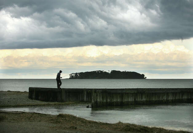 A fisherman tries his luck as storm clouds roll in over Walnut Beach and Charles Island in Milford on Monday, June 25, 2012. Photo: Brian A. Pounds / Connecticut Post