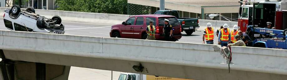 Workers remove a section of the highway barrier on Interstate 35 southbound near McCullough Ave. after a rollover wreck Monday June 25, 2012. Photo: Edward A. Ornelas, San Antonio Express-News / © 2012 San Antonio Express-News