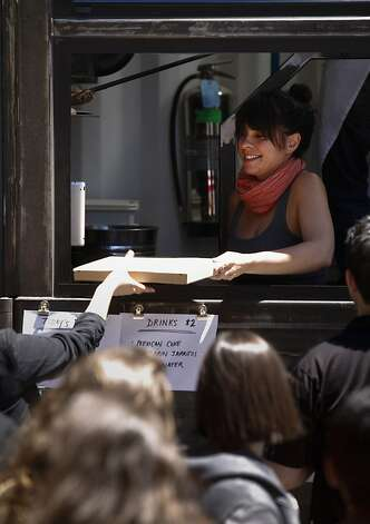 Niki Shelley hands a pizza to a customer at Jonathan Darsky's Del Popolo, a mobile pizzeria housed in a 25ft. shipping container, on Thursday, June 7, 2012 at Mint Plaza in San Francisco, Calif. Photo: Russell Yip, The Chronicle