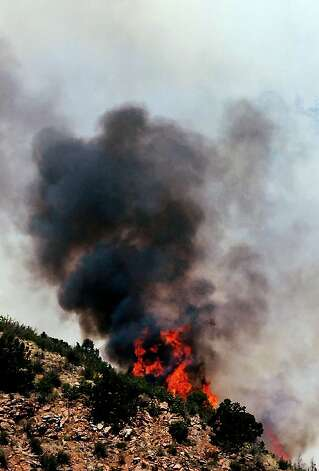 The Waldo Canyon wildfire blazes through tree tops west of Manitou Springs, Colo., Monday, June 25, 2012. The Waldo Canyon fire, one of at least a half-dozen wildfires in Colorado on Monday, has blackened 5.3 square miles and displaced about 6,000 people since it started Saturday, June 23, but no homes have been destroyed. (AP Photo/Ed Andrieski) Photo: Ed Andrieski, Associated Press