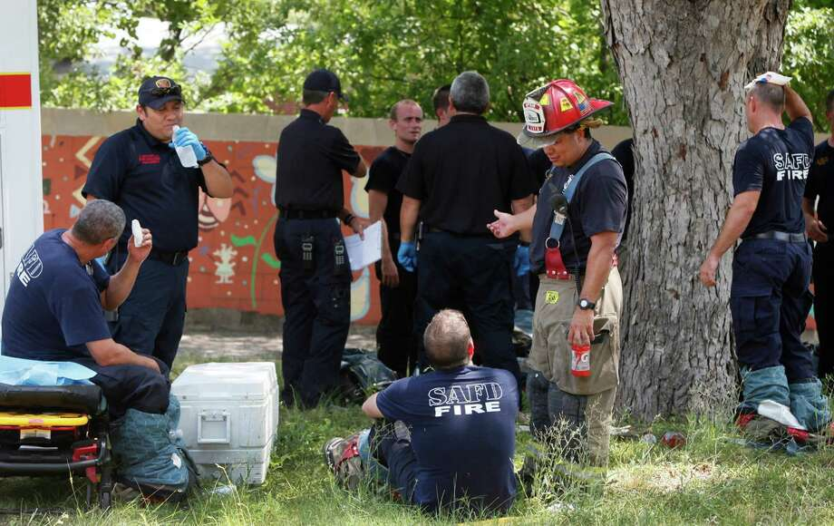San Antonio firefighters cool off under a large pecan tree after fighting a fire Monday June 25, 2012 at 318 West Ligustrum. The fire broke out after 2:00 p.m. and the home's owner Julian Menchaca said a water heater malfunctioned, causing the blaze. Photo: John Davenport, San Antonio Express-News / John Davenport/San Antonio Express-News