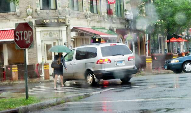A woman is nearly run over during a burst of rain as she crosses Forest Street in Stamford, Conn., June 25, 2012. Photo: Keelin Daly / Stamford Advocate
