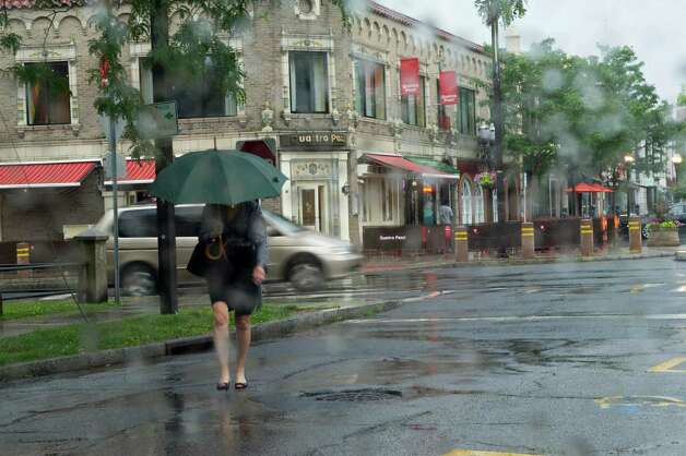 A woman walks in the rain along Prospect Street in Stamford, Conn., June 25, 2012. Photo: Keelin Daly / Stamford Advocate