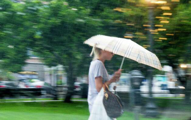A woman is caught in a blast of rain as she walks along Latham Park in Stamford, Conn., June 25, 2012. Photo: Keelin Daly / Stamford Advocate