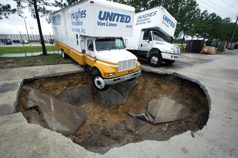 A truck hangs over the edge of a sinkhole that opened up in the parking lot of Hughes Relocation Services, Monday, June 25, 2012, in Salt Springs, Fla. Tropical Storm Debby raked the Tampa Bay area with high wind and heavy rain Monday in a drenching that could top 2 feet over the next few days and trigger widespread flooding. Photo: AP