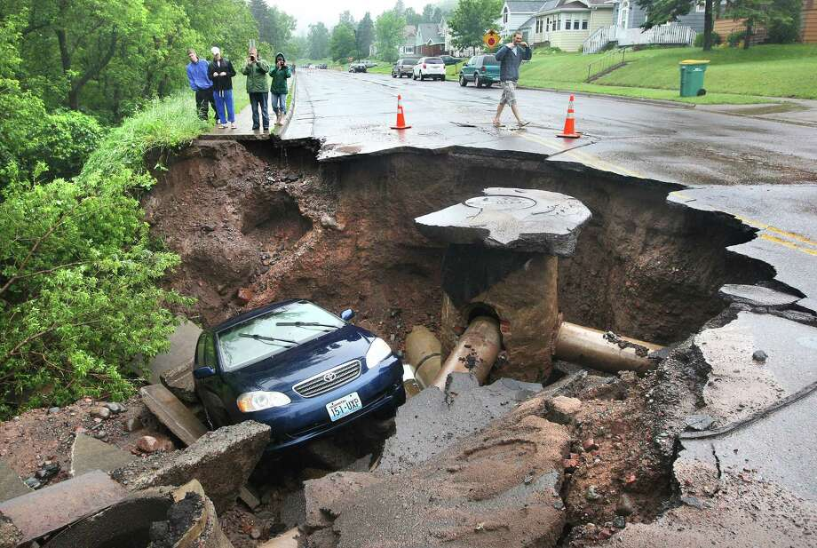 A car fell into a huge sinkhole in Duluth, Minn. on Wednesday, June 20, 2012.  Photo: AP