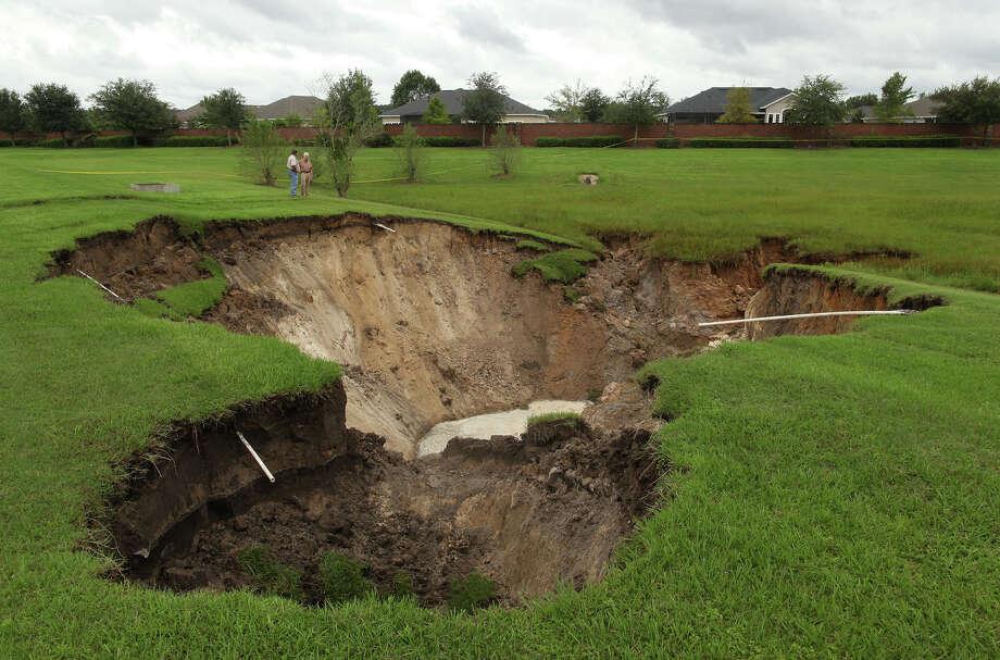 People look at a large sinkhole near Jonesville Park Monday, June 25, 2012, in Jonesville, Fla.  Photo: AP