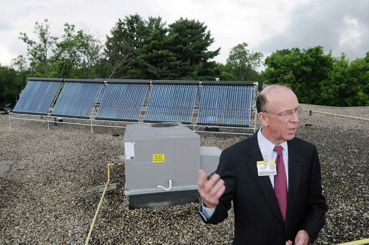 David Kruczlnicki, president and CEO of Glens Falls Hospital, stands on the roof of the hospital's Renal Dialysis Center on Monday, June 25, 2012 in Glens Falls, NY. A media event was held on Monday to show the installed solar thermal system, seen in the background. The Center uses 200 gallons of heated water per hour for patient treatment, and now has become one of the first in the U.S. to use solar thermal technology for dialysis treatments. (Paul Buckowski / Times Union)