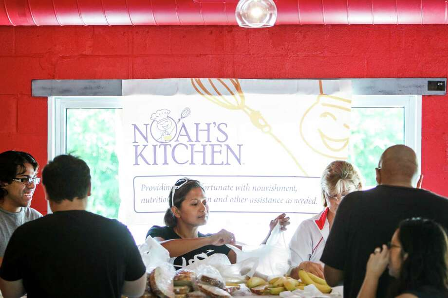 Regina Eco, center, and other volunteers with Noah's Kitchen prepare food for the last time at Jenni's Noodle House on Sunday, pending success or failure of a petition to overturn a new homeless feeding ordinance. Photo: Michael Paulsen / © 2012 Houston Chronicle