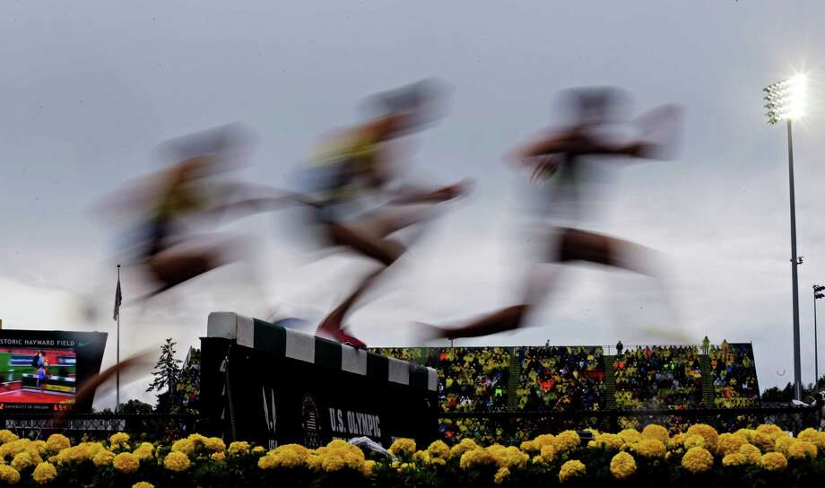 Runners clear a water jump during a men's 3,000m steeplechase preliminary at the U.S. Olympic Track and Field Trials Monday, June 25, 2012, in Eugene, Ore. Photo: Matt Slocum, Associated Press / AP