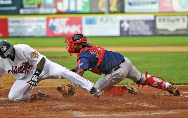 Tri-City ValleyCats player Emilio King crosses home to make the score 3-0 in the bottom of the fourth inning, as Lowell Spinners catcher Oscar Perez is too late with the tag,  on Monday night June 25, 2012 in Troy, NY.(Philip Kamrass / Times Union) Photo: Philip Kamrass / 00018017A