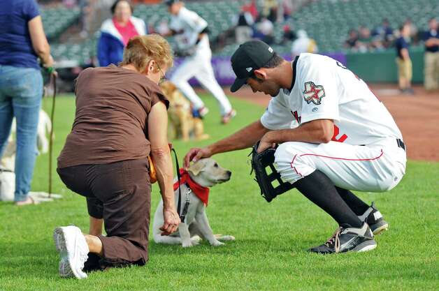 "Tri-City ValleyCats player Justin Gominsky visits with Cobey, a dog who helps blind people, and Diana Traegler of Altamont on the field during ""Bark in the Park"" night during the ValleyCats game against the  Lowell Spinners on Monday night June 25, 2012 in Troy, NY.(Philip Kamrass / Times Union) Photo: Philip Kamrass / 00018017A"