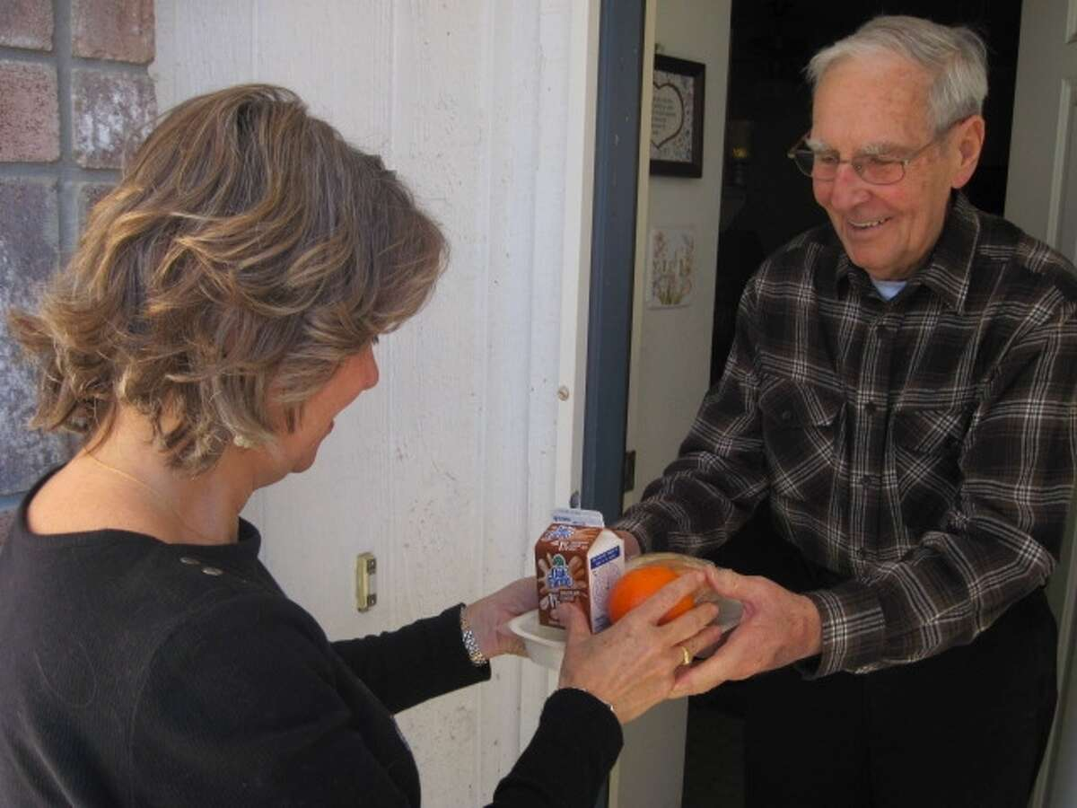 Volunteers such as Zora Bilicich donate one hour a day to deliver hot, nutritious meals to homebound seniors like John Murphy.