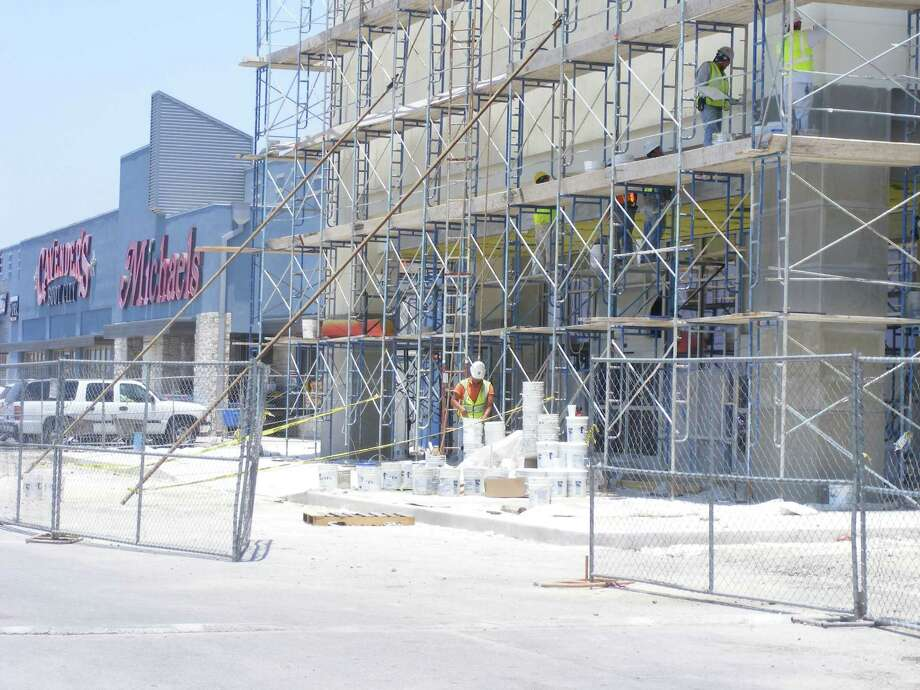 Workers tend to the facade of the Ross Dress For Less store that is part of the renovated Windcrest Park Centre shopping center along Interstate 35. Photo: Jeff B. Flinn / NE Herald