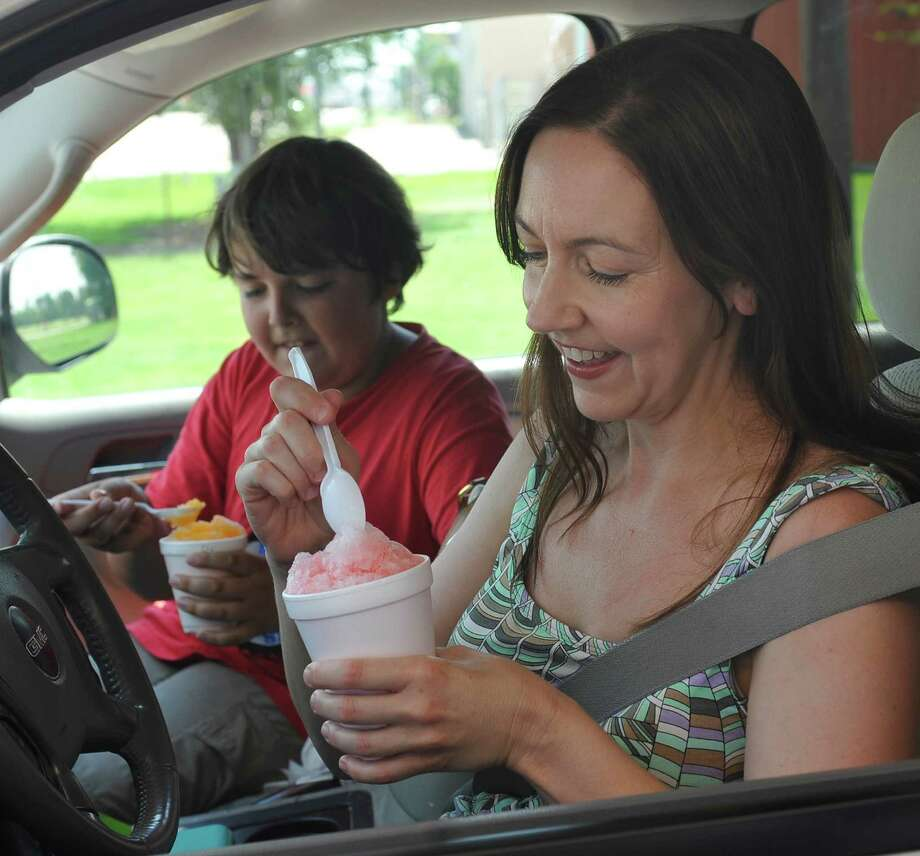 Katrina Alexander, right, and her son John, left, enjoy their snow cones, made by hand by Cecile Jimenez, manager of the Sno Biz on College Street Street next to Games People Play. John had just come off of tennis lessons Monday June 25, 2012.   Nothing says summer like snow cones, and as it has begun to get uncomfortably hot over Southeast Texas, snow cone season is here. Snow ball vendors feel there is a direct correlation between the heat and demand for the icy summer treat. There are several stands around Beaumont.  Dave Ryan/The Enterprise Photo: Dave Ryan