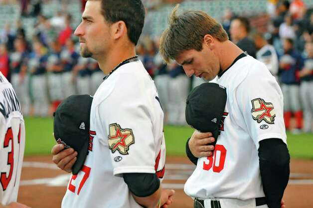 Tri-City ValleyCats players Andrew Aplin, left, and Mike Cokinos, right, stand at attention for the singing of the National Anthem before their game with the Lowell Spinners on Monday night June 25, 2012 in Troy, NY. (Philip Kamrass / Times Union) Photo: Philip Kamrass