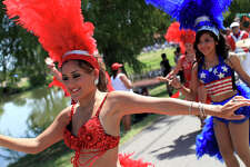 "metro - Dancers including Mitzy Ramirez, left, and Debbie Reyes, right, and drummers with Samba Vida Performance Company dance during the ""Salute to the Red, White and Blue Parade"" at Woodlawn Lake Park in San Antonio on Monday, July 4, 2011. LISA KRANTZ/lkrantz@express-news.net"