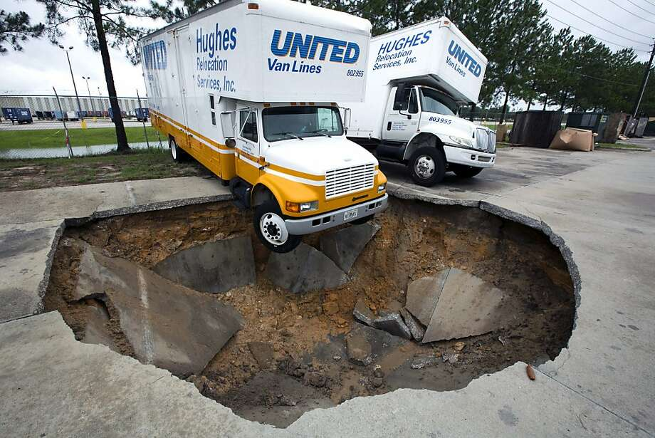 Hello, Mr. Pendersnap? We may be a little late delivering your furniture ...A sinkhole that opened up in the parking lot of Hughes Relocation 