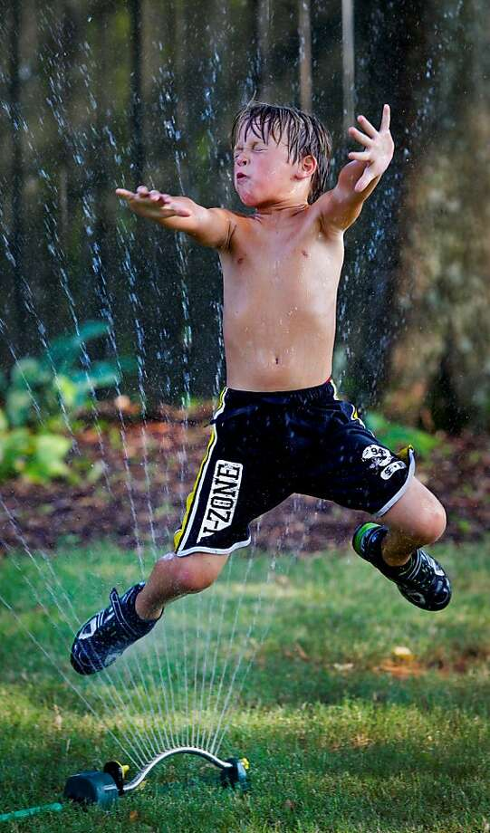 Tyce Moody jumps through a lawn sprinkler to cool off and have fun on a hot 101 degree Monday afternoon June 25, 2012, in Huntsville, Ala. (AP Photo/The Huntsville Times, Glenn Baeske) Photo: Glenn Baeske, Associated Press
