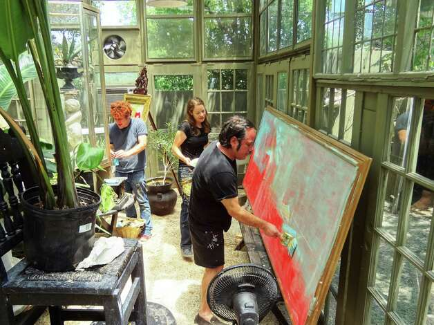 San Antonio artist Franco Mondini-Ruiz repaints a large canvas in his greenhouse studio with assistants Bryson Brooks and Holly Hein Brooks. The canvas is being repurposed into a landscape in homage to early Texas painters the Onderdonks.