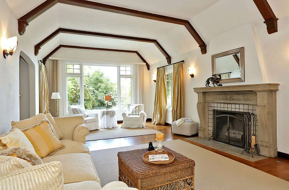 The living room has a wood-burning fireplace, tall vaulted ceilings and French doors. Photo: Liz Rusby