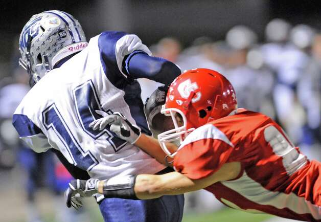West Orange-Stark Mustang #14, J Marcus Rhodes, holding on tight to the ball despite the best effort of a Columbus Cardinals defensemen trying  to bring him down in first half action against the Columbus Cardinals at Moorehead Stadium in Conroe Texas.  Dave Ryan/The Enterprise Photo: Dave Ryan