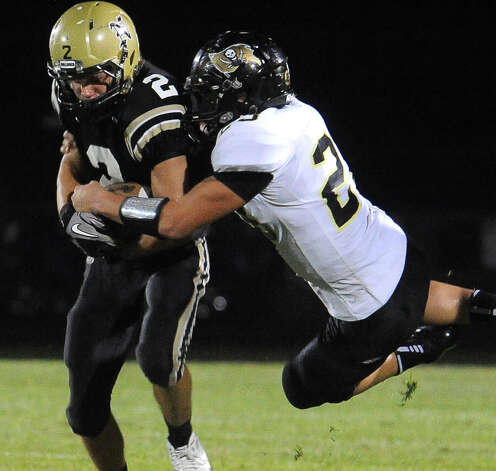 Nederland's Michael Shaw carries the balls as Vidor's Montana Quirante goes for the tackle at Bulldog Stadium in Nederland, Friday, September 23, 2011   Tammy McKinley/The Enterprise Photo: TAMMY MCKINLEY