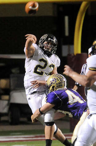 Vidor's Montana Quirante releases the pass just before being hit by Montgomery's Jesse Hooper at Thorne Stadium in Aldine, Friday, November 18, 2011. Tammy McKinley/The Enterprise Photo: TAMMY MCKINLEY