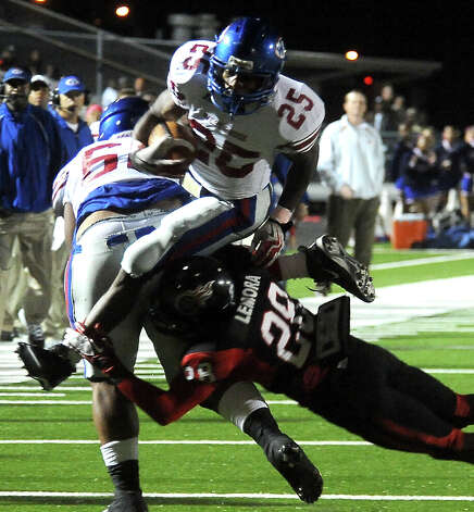 West Brook's Justin Hervey attempts to leap over Memorial's Darius Lemora at Memorial Stadium in Port Arthur, Friday, October 21, 2011. Tammy McKinley/The Enterprise Photo: TAMMY MCKINLEY