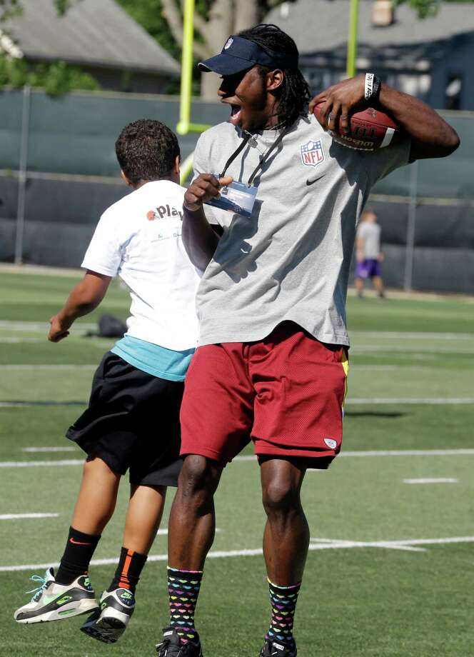 "Washington Redskins quarterback Robert Griffin III celebrates with a youngster during a youth camp as part of the NFL football rookie symposium at the Cleveland Browns training facility in Berea, Ohio Tuesday, June 26, 2012. A former Baylor basketball player is facing a federal extortion charge for allegedly threatening to release ""derogatory information"" about Heisman Trophy winner Robert Griffin III unless he was paid. Photo: AP"