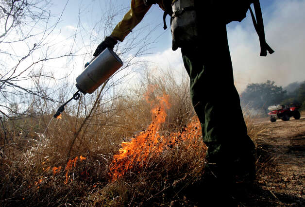 A drip torch is used  Thursday Dec. 6, 2007 to start a fire during a prescribed burn at Government Canyon State Natural Area in Bexar County. Photo: WILLIAM LUTHER, SAN ANTONIO EXPRESS-NEWS / SAN ANTONIO EXPRESS-NEWS