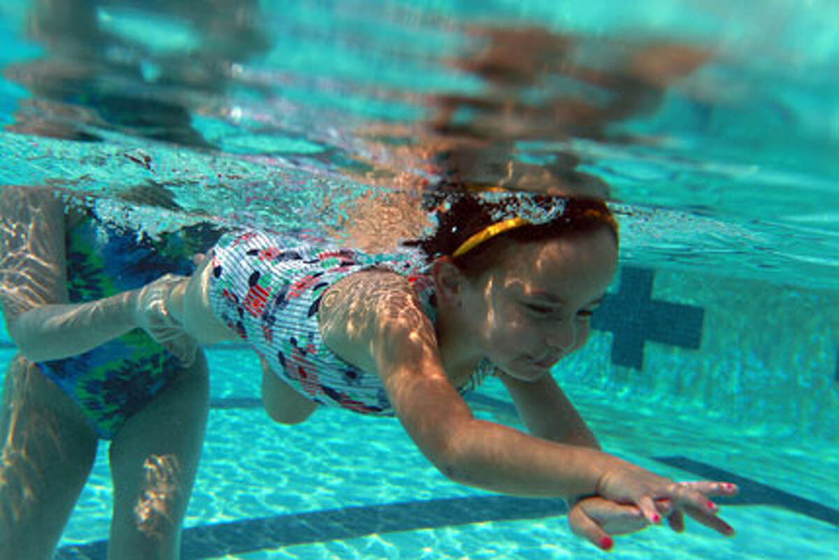Sophia Pawlak, 3, gets a push from swim instructor Faith
