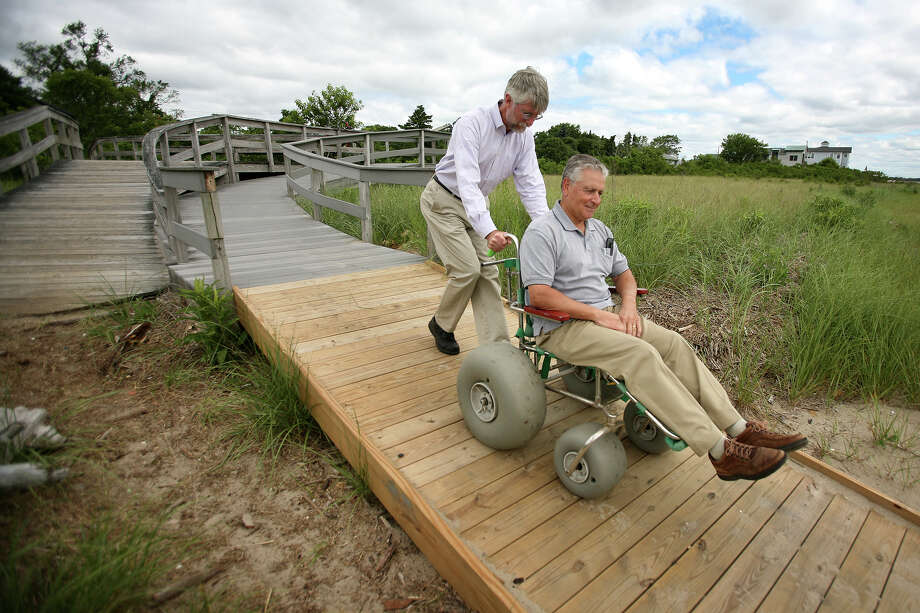 Tom Andersen, Connecticut Audubon communications director, left, and Don Chiboucas, president of the Wheels in the Woods foundation, demonstrate the new wheelchair ramp at Audubon's Milford Point preserve in Milford on Tuesday, June 26, 2012. Photo: Brian A. Pounds / Connecticut Post