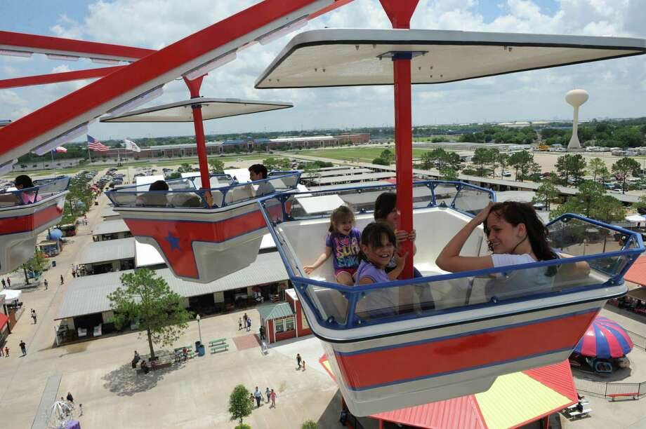 "A group of kids take a spin on the new ""Star Dancer"" ride at Traders Village. The ride combines a carousel and gondola wheel on an 80-foot tower. Photo: Thomas Nguyen / Freelance"