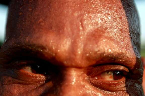 Sweat beads on the face of J.C. Wright who was doing pull-ups at Hutcheson Park on June 26, 2012. Wright who works out weekdays said the heat doesn't bother him. (Johnny Hanson / Houston Chronicle)