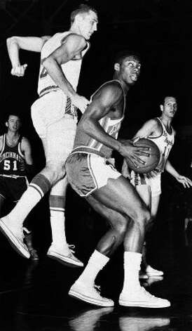 In this Feb. 5, 1961, file photo, Cincinnati Royals' Oscar Robertson, center, looks back as Los Angeles Lakers' Jerry West defends during their NBA basketball game in Morgantown, W.Va. (AP Photo, File) (AP)