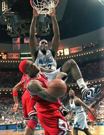 The Magic's Shaquille O'Neal  dunking the ball and knocking Chicago Bulls' Dennis Rodman out of the way at the same time during their game in Orlando in 1996. (AP Photo/Steve Simoneau) (AP)