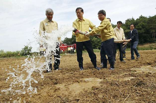 South Korean Prime Minister Kim Hwang-sik, second from left, waters a dried-up rice paddy while inspecting farmland hit by months of drought in Hwaseong, South Korea, Tuesday, June 26, 2012. South Korean officials reported the worst drought in more than a century in some areas after nearly two months without significant rainfall, raising worries about damage to crops and a dangerous drop in water levels at the nation's reservoirs. (AP Photo/Yonhap, Lee Jung-hoon) KOREA OUT Photo: Lee Jung-hoon, Associated Press