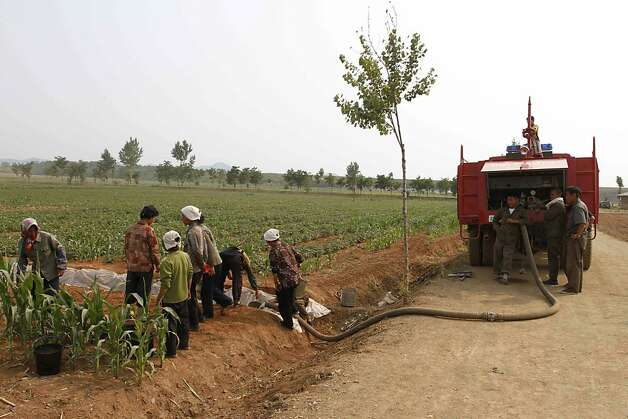 In this Friday, June 22, 2012 photo, North Koreans use a truck to pump water into a field in Kohyon-ri, North Korea in the country's Hwangju County. Both Koreas are suffering from the worst dry spell since record keeping began more than a century ago, according to officials in Seoul and Pyongyang. (AP Photo/Kim Kwang Hyon) Photo: Kim Kwang Hyon, Associated Press