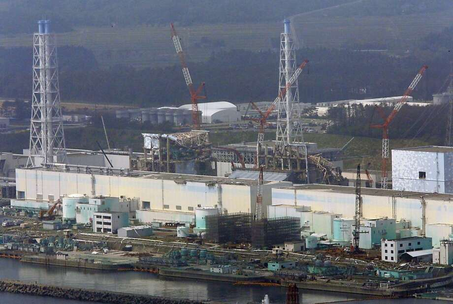 In this aerial photo taken from the Asahi Shimbun helicopter, cranes surround the tsunami-damaged Fukushima Dai-ichi nuclear power plant reactors, from right, Unit 2, covered by light blue walls, Unit 3, center, and Unit 4, in Okuma, Fukushima Prefecture, northeastern Japan, Monday, May 28, 2012. The prime minister during Japan's nuclear crisis last year said Monday he had to use an emergency law that never anticipated major radiation leaks and lacked experts capable of giving him guidance. (AP Photo/Tom Curley) Photo: Tom Curley, Associated Press