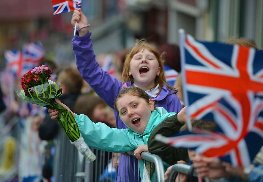 ENNISKILLEN, NORTHERN IRELAND - JUNE 26:  Children wave Union Jack flags and hold out floral bouquets as Queen Elizabeth II and Prince Philip, Duke of Edinburgh arrive to visit Macartin's Cathedral on June 26, 2012 in Enniskillen, Northern Ireland. The Queen and Duke of Edinburgh, on a Diamond Jubilee visit to Northern Ireland, are due to meet with former IRA leader and NI's Deputy First Minister Martin McGuinness.  (Photo by Jeff J Mitchell/Getty Images) Photo: Jeff J Mitchell, Getty Images